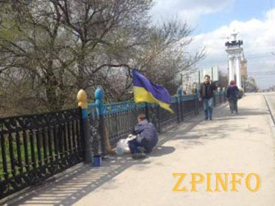 В центре Запорожья закрашивают сине-желтый забор