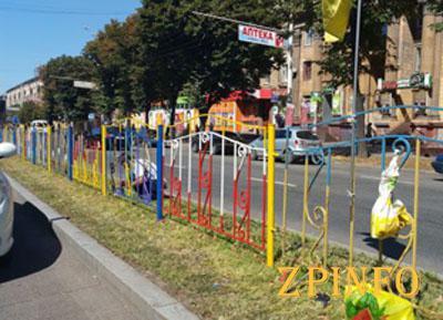 В центре Запорожья желто-голубой забор красят в разные цвета